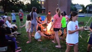 Kids having fun around the campfire at the coolest summer camp in Minnesota
